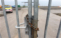 A fence is locked and patrolled near where robbers entered the airport. Trip wires are now being discussed as a way to monitor the extensive fencing surrounding airports.