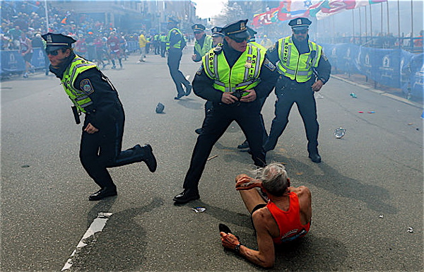 Police officers react to a second explosion at the finish line of the Boston Marathon. | John Tlumacki Photo