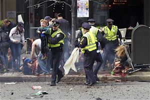 A police officer carries a wounded child from the scene of the second blast near the finish line of the Boston Marathon. | Photo by Bill Hoenk.